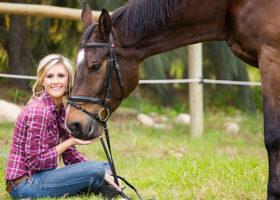 Kvinna i rutig skjorta sitter på en äng och håller i sin hästs grimma