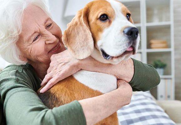 Äldre kvinna kramar om hund