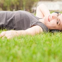 Kvinna ligger i gräset och lyssnar med lurar på