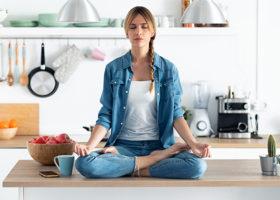 Kvinna sitter i skräddarställning på köksbänk