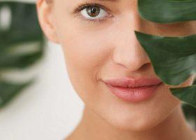Närbild på kvinna bakom gröna blad