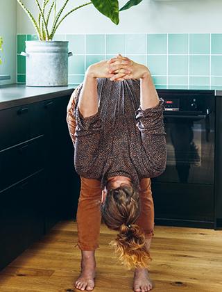 Kvinna står i yogaposition i köket med huvudet ner och händerna sammanflätade bakom ryggen
