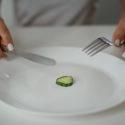 två händer med bestick och en gurkbit på en tallrik