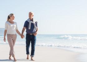 Medelålders par går hand i hand på strand