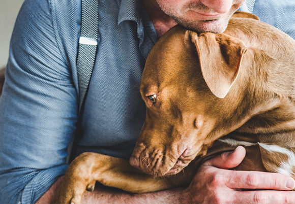 Man med en hund i sin famn