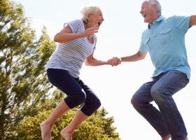 Äldre par hoppar upp i luften