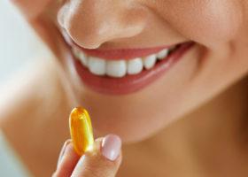 Leende kvinna håller i kosttillskott