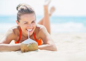 kvinna med drink på stranden