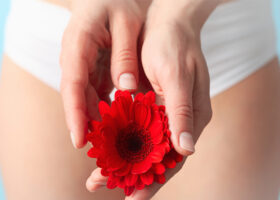 kvinna håller blomma framför underlivet