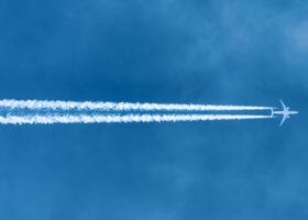 Flygplan lämnar bränslespår på blå himmel