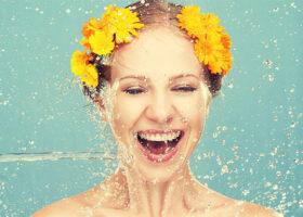 Kvinna med gula blommor i håret får vatten stänkt på sig