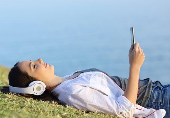 Ung kvinna ligger ner vid havet och lyssnar i hörlurar