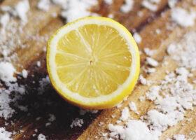 Träskärbräda med en halv citron och flingsalt på