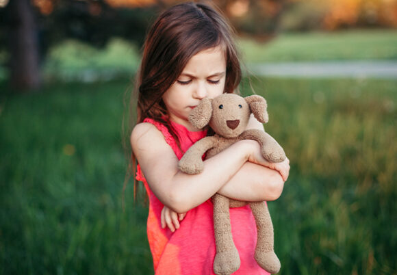 Liten flicka kramar en nalle ute i en park