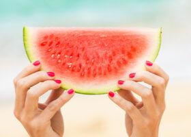 Två händer håller i vattenmelon på strand