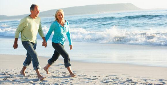 Par promenerar på stranden