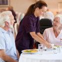 kvinna serverar seniorer mat