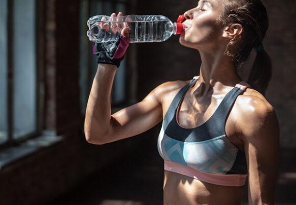 svettig kvinna dricker vatten