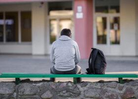 ung kille sitter med ryggen till på en bänk