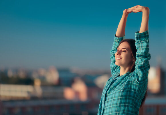ung glad kvinna sträcker upp händerna