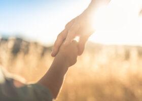 Vuxens hand håller i barns hand i motljus