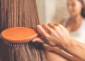 Brunhårig kvinna borstar håret