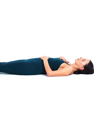 Sara Emilionie yoga-andas liggande på rygg