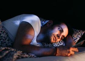 man i sängen tittar i smartphonen
