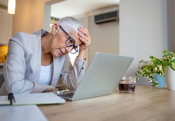 trött kvinna framför dator