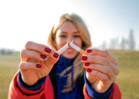 kvinna bryter av cigarett
