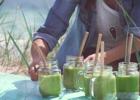 Gröna smoothies med sugrör serveras på stranden
