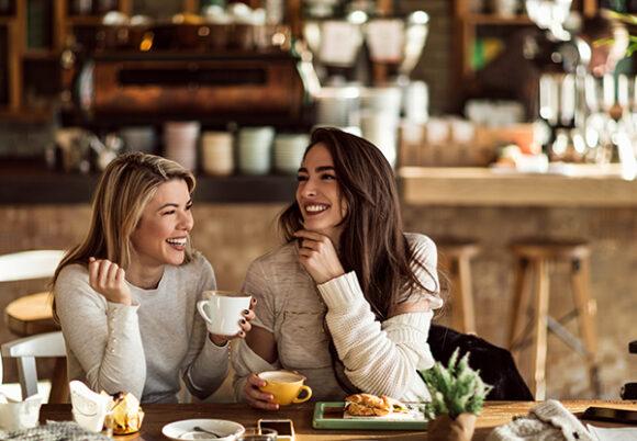 Två kvinnliga vänner skrattar vid ett cafébord