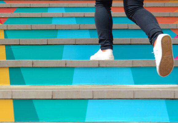 Ett par ben som går i färgglada trappor
