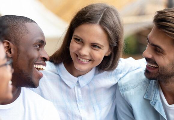Fyra vänner ler och håller om varandra