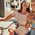 Två kvinnor håller skrattandes i en cykel
