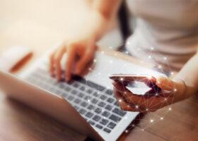 Närbild på dator och mobil i knät på kvinna
