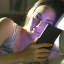 Kvinna i sängen med mobil i handen