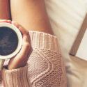 Närbild på kvinnas ben och kaffekopp i handen