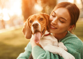 Ung kvinna omfamnar sin hund